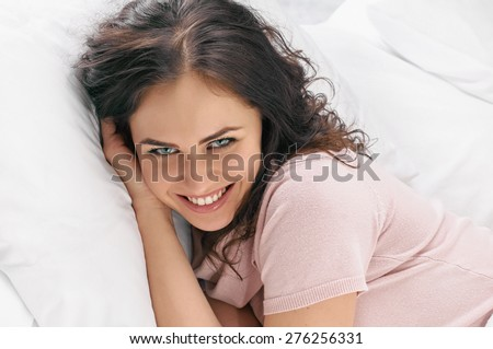 Young beautiful happy woman waking up on bed, close up - stock photo