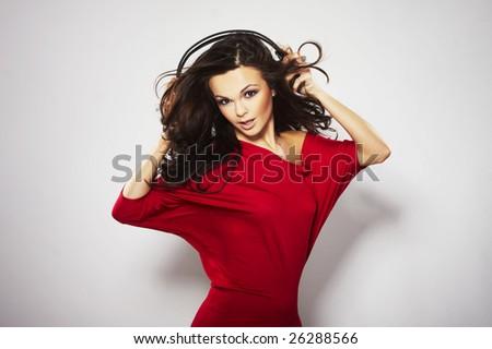 Young beautiful happy women listening music in headphones in read dress - stock photo