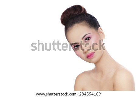Young beautiful healthy asian girl with shiny pink makeup and hair bun over white background, copy space - stock photo