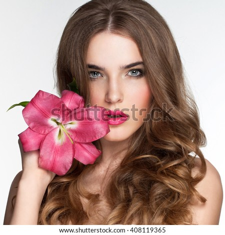Young beautiful healthy blond girl with pink flower on white background. - stock photo