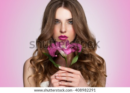 Young beautiful healthy blond girl with red flower on pink background. - stock photo