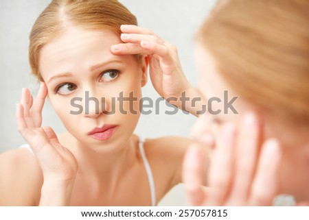 young beautiful healthy woman  frightened saw in the mirror acne and wrinkles - stock photo