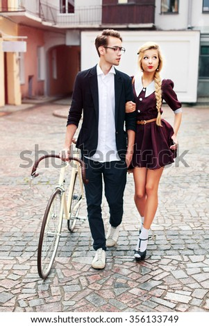 Young beautiful hipster couple vintage style posing outdoor on the street fashion style having fun together walking