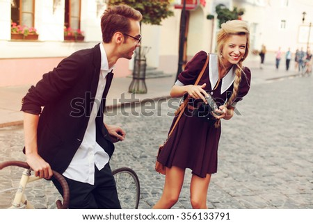 Young beautiful hipster couple vintage style posing outdoor on the street fashion style having fun together laughing  - stock photo