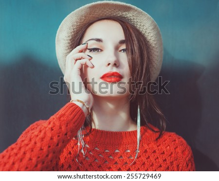 Young beautiful hipster girl in red jersey with hat outdoor  - stock photo