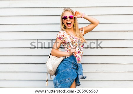 young beautiful hipster girl in sunglasses posing on wall background. Blonde laughs in shorts, t-shirt with a backpack standing near the wall  - stock photo