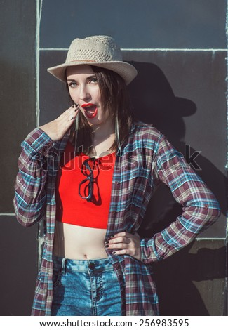 Young beautiful hipster girl in the hat surprised outdoor near wall - stock photo