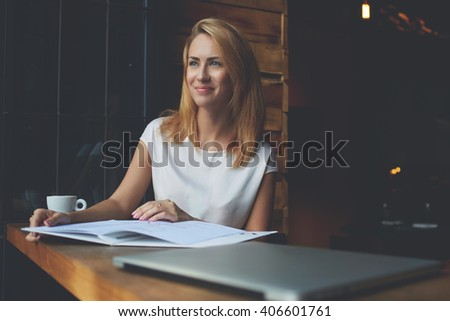 Young beautiful hipster girl with good mood sitting with big notepad in coffee shop during her recreation time, charming Caucasian woman enjoying calm and rest after work on her laptop computer  - stock photo
