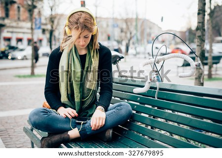 young beautiful hipster sporty blonde woman sitting with leg crossed on a bench with bike, using smartphone looking down the screen, listening music with headphones - relaxing, technology concept - stock photo