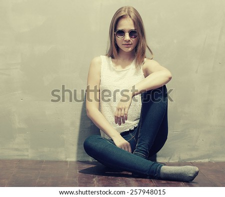 young beautiful hipster woman portrait in glasses and knitted clothes near grange wall vintage black and white - stock photo