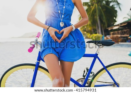 young beautiful hipster woman posing with bicycle on beach, showing heart with hands, gesture, concept, details, summer vacation, vintage style, boho outfit, blue dress, slim body, bright, colorful  - stock photo