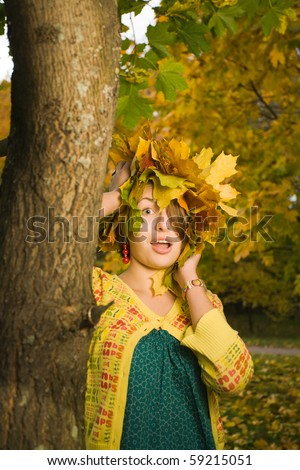 Young beautiful homely woman with crown of maple leaves in autumn park - stock photo