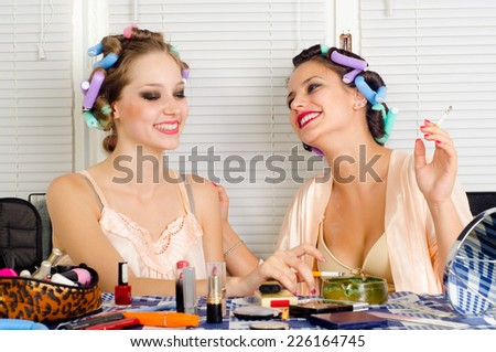 Young beautiful housewife telling funny story to her friend. - stock photo