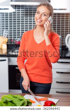 Young beautiful housewife woman cooking in a kitchen while talking by mobile phone - stock photo