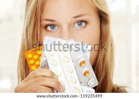 Young beautiful ill woman with pills.
