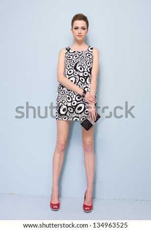 Young beautiful in stylish woman with purse in studio - stock photo