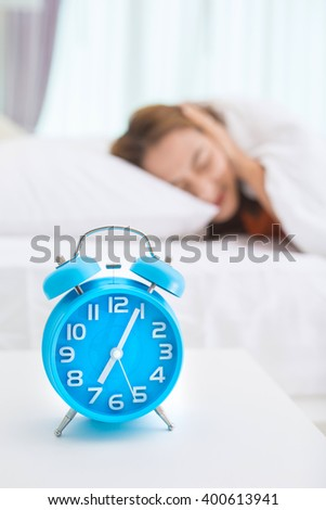 Young beautiful in the morning. Girl looking at alarm clock and trying to hide under the pillow - stock photo