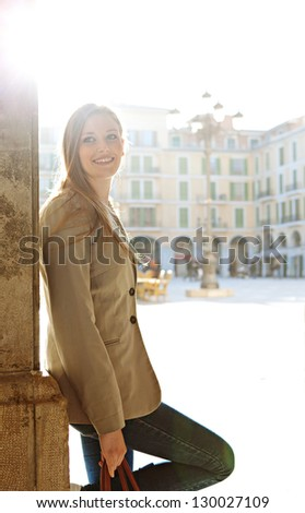 Young beautiful independent woman tourist visiting a destination city and leaning on an old column with the sun shining directly behind her, smiling. - stock photo