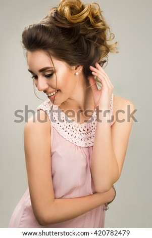 Young beautiful lady in tender pink dress posing in studio on grey background. not isolated.Supple wedding make up hairstyle and neutral lips.Gorgeous spring portrait. Charming face, stunning smile - stock photo