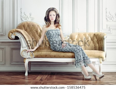 young beautiful lady on the vintage sofa - stock photo