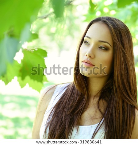 young beautiful lady outdoor portrait, girl with long brown hair posing in  in summer park  - stock photo