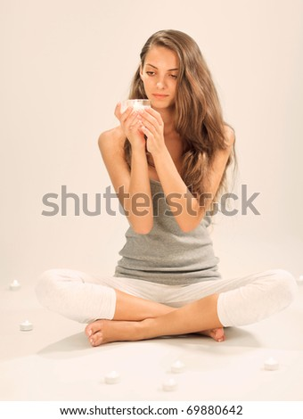 Young beautiful lady relaxing with candle in studio on white