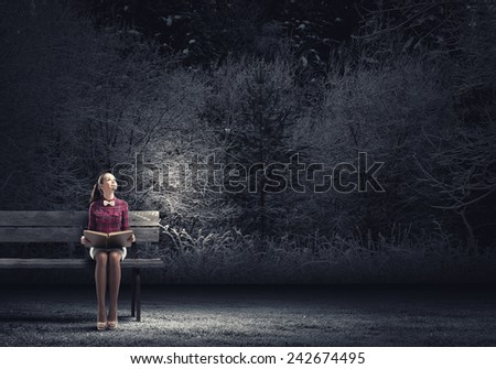 Young beautiful lady sitting on bench and reading book - stock photo