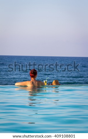 Young Beautiful Lady Standing in Swimming Pool with Cocktail, Glasses, Hat and looking at the Sea, Crete
