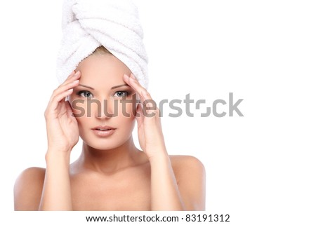 Young beautiful lady with a towel on her head touching temples - stock photo