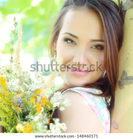 young beautiful lady with field flowers outdoor portrait, charming girl resting in summer park, toned and noise added - stock photo