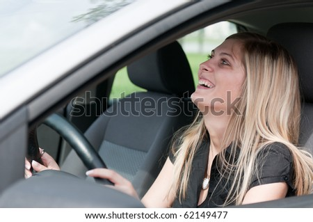 Young beautiful laughing woman driving car - portrait through side window - stock photo