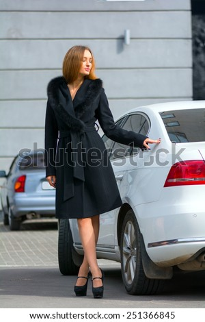 Young beautiful leggy chestnut in a black coat with a fur collar standing near the white car - stock photo