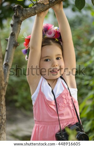 Young beautiful little girl wearing flower wreath holding around the neck old vintage film photo camera playing outdoor swinging on a twig. Children's play. Art or creativity concept. - stock photo