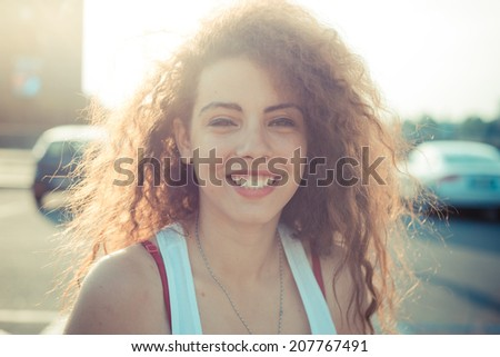 young beautiful long curly hair hipster woman in the city - stock photo