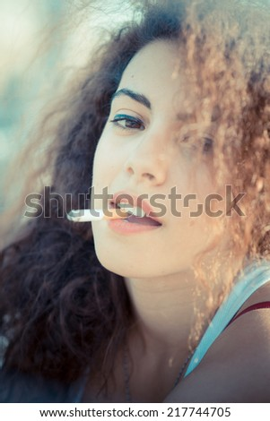 young beautiful long curly hair hipster woman smoking  in the city