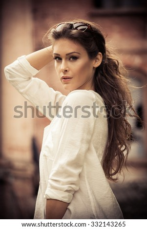 young beautiful long hair woman portrait, outdoors in the city, wearing white shirt, autumn day - stock photo