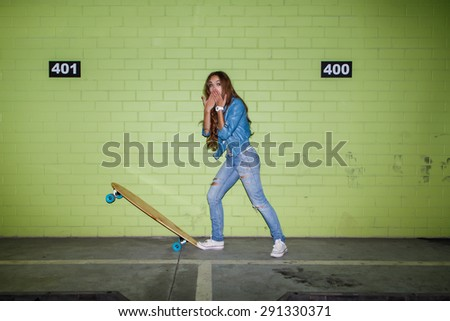 young beautiful long-haired brunette lady with wooden longboard skateboard coquettishly sending an air kiss near the green brick wall - stock photo