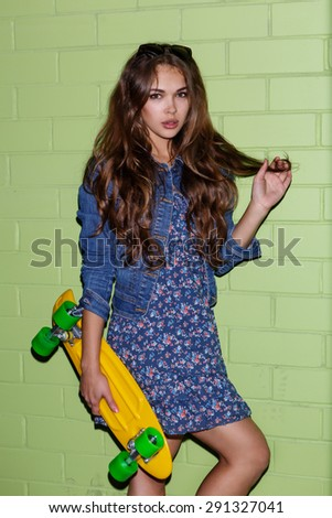 young beautiful long-haired girl with plastic penny skateboard coquettishly corrects her hairs near the green brick wall - stock photo