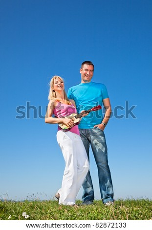 Young beautiful lover play music on guitar in park - stock photo