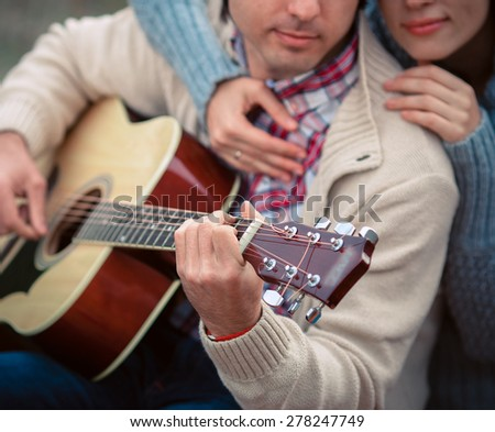 Young beautiful lovers playing guitar - stock photo