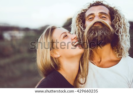 Young beautiful loving couple, a blonde Girl and laughs together with her beautiful Bearded man, Crazy guys, hipsters, Fun and creative, outdoor portrait, close up  - stock photo
