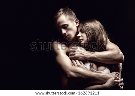 Young beautiful loving couple is embracing on a black background