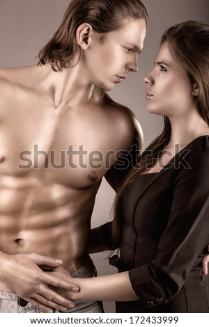 Young beautiful loving couple is embracing on a gray background