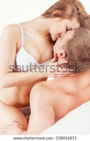 Young beautiful loving couple is embracing on a white background - stock photo