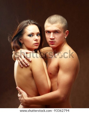 Young beautiful loving couple is embracing - on black background