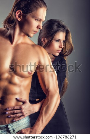 Young beautiful loving couple on a dark background. Focus on girl