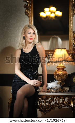 Young beautiful luxurious woman in long elegant black dress. Beautiful young blonde woman with bright lights in background. Seductive blonde woman in luxury manor, vintage style - stock photo