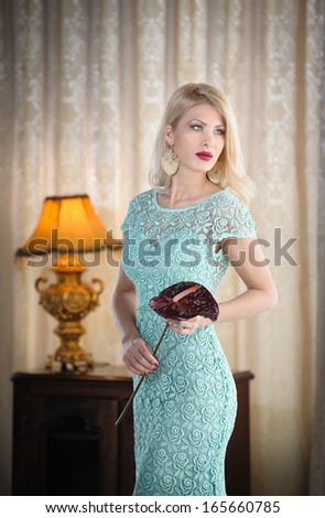 Young beautiful luxurious woman in long elegant dress. Beautiful young blonde woman in turquoise dress with curtains in background. Seductive blonde woman in lace dress in luxury manor, vintage style - stock photo