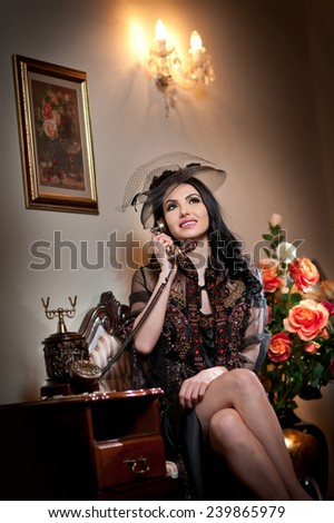 Young beautiful luxurious woman in long elegant dress talking by phone in a elegant scenery. Seductive brunette woman with roses in background holding a vintage phone in luxurious classic interior - stock photo