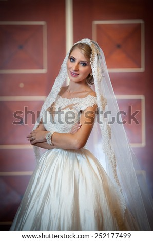 Young beautiful luxurious woman in wedding dress posing in luxurious interior. Gorgeous elegant bride with long veil. Full length portrait of seductive blonde bride with fashionable gown, indoor shot - stock photo